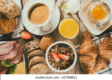 breakfast of coffee, juice, muesli, breads, ham and cheese - top view, toned