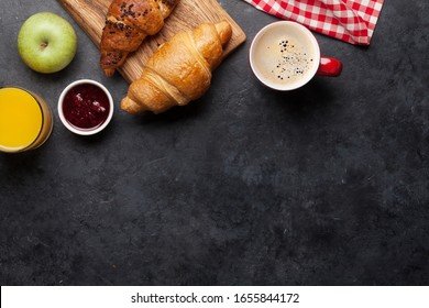Breakfast with coffee, orange juice, jam and croissant. Top view on stone table with copy space. Flat lay
