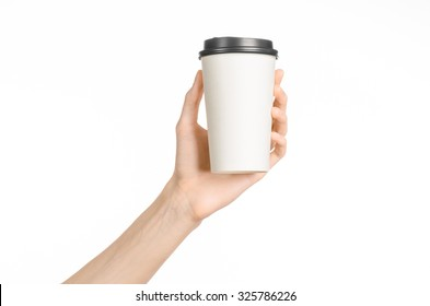 Breakfast and coffee theme: man's hand holding white empty paper coffee cup with a brown plastic cap isolated on a white background in the studio, advertising coffee