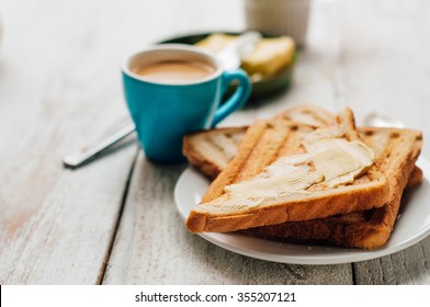 Breakfast with coffee, toasts, butter and jam on white wooden background