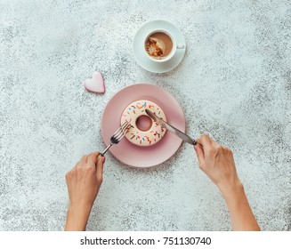 Breakfast concept: Close up of female hands with fork and knife cutting donut shape biscuit on white stone background; top view, flat lay