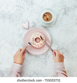 Breakfast concept: Close up of female hands with fork and knife cutting donut shape biscuit on grey stone background; top view, flat lay