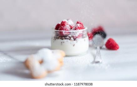 Breakfast concept with fresh yoghurt, berries and muesli, selective focus