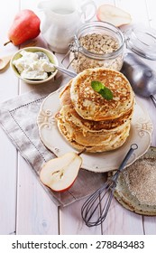 Breakfast concept. Stack of healthy low carbs oat pancakes with cottage cheese and fruits over white wooden background