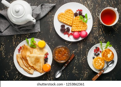 Breakfast - crepes, wafers and pancakes on white plates on a dark background. Top view.