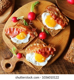 Breakfast , crispy bacon, fried eggs and bread. Sandwiches on cutting board. Rustic table . Top view
