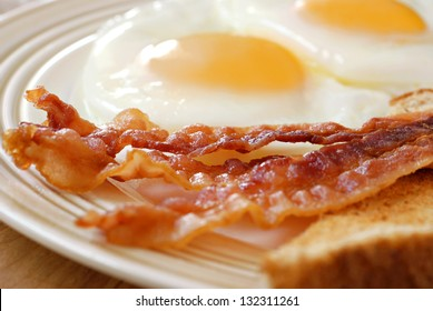 Breakfast of crispy bacon, fried eggs and toast.  Macro with extremely shallow dof.