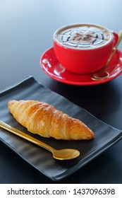 Breakfast croissant and​ cappuccino coffee on table