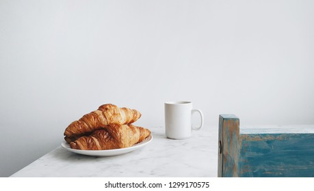 Breakfast croissant and coffee on marble table