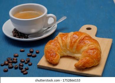 Frühstückskreuz und heißer Kaffee auf blauem Hintergrund