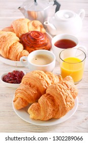 Breakfast, with croissant, juice and coffee over wooden background