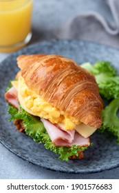 Breakfast croissant sandwich with scrambled eggs and ham on a blue plate, closeup view
