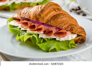 breakfast of croissant  stuffed with salami and brie on white wooden background