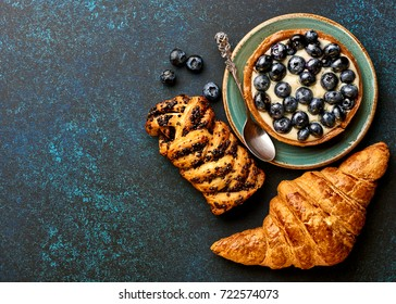 Breakfast with croissant, tart. Bakery products with copy space.