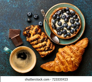 Breakfast with croissant, tart and coffee. Bakery products.