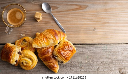 Breakfast with croissants, cinnamon buns and chocolate cookies, fresh orange juice and coffee on the side on a wooden background. Top view.