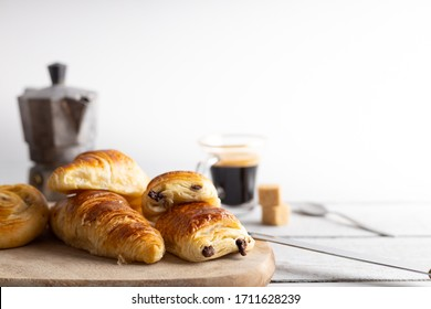 Breakfast with croissants, cinnamon buns and chocolate cookies, fresh orange juice and coffee on the side on a white background.