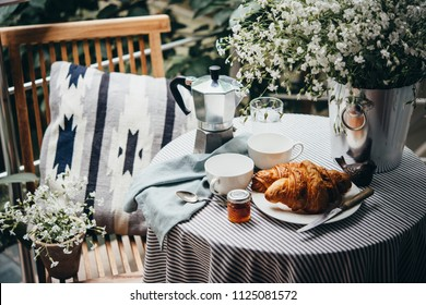 Breakfast with croissants and coffee served on a beautiful terrace or balcony
