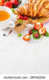 Breakfast - croissants with strawberry, blackberry, raspberry on wood board, tea, jam, white wood background