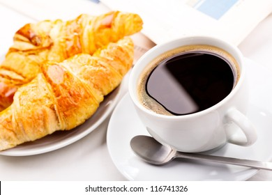 breakfast with cup of black coffee, croissants and newspaper