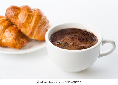 Breakfast with cup of black coffee and croissants.