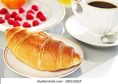 Breakfast. A cup of coffee, croissant and berries