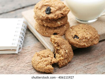 Breakfast with cup of milk and cookies on wooden background.