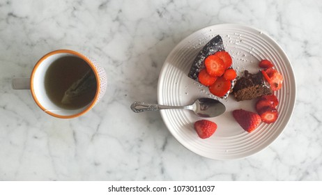 Breakfast cup of tea and chocolate cake with strawberries