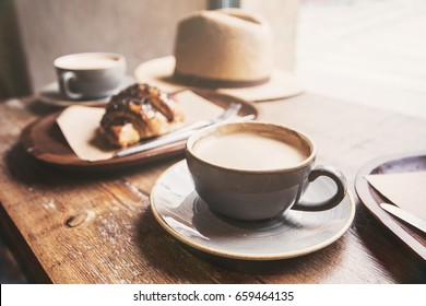 Breakfast, cups of coffee and fresh croissant on a table in a coffee shop