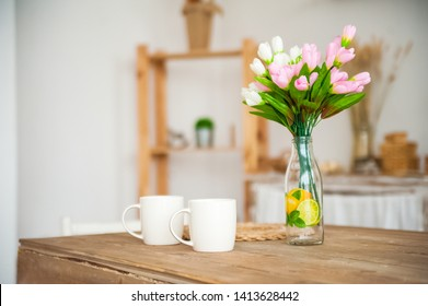 Breakfast cups and fruit. Spring tulips on the table. Wooden table in a bright rustic-style kitchen. Scandinavian style in the interior of the kitchen.