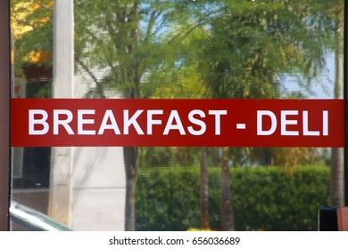 Breakfast - Deli White Letters on Red Banner Stuck on Storefront Window, Glass Reflecting Palm Trees and Bushes