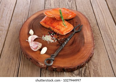 breakfast delicious portion of fresh roast salmon fillet with dry spices garlic and rosemary on wooden plate with black forged handmade fork healthy food diet cooking concept