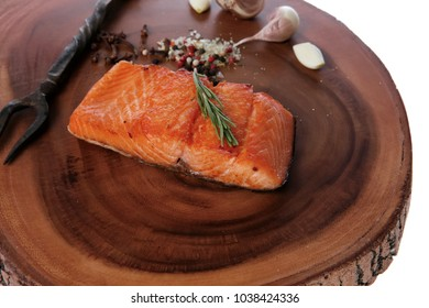 breakfast delicious portion of fresh roast salmon fillet with dry spices garlic and rosemary on wooden plate with black forged handmade fork healthy food diet cooking concept isolated white background