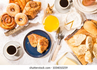 Breakfast with different French Pastries, such as Almond Croissants, Donuts and Pain Au Raisins, also with Baguette Bread, Cheese, Jam, Juice and Coffee