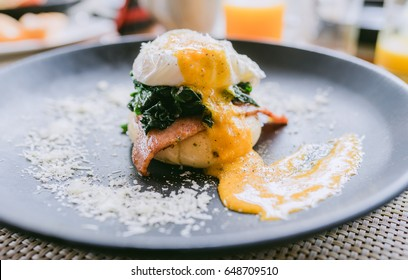 Breakfast is Egg Benedict on black plate .Eggs Benedict- toasted English muffins, ham, poached eggs,spinach and delicious buttery hollandaise sauce.