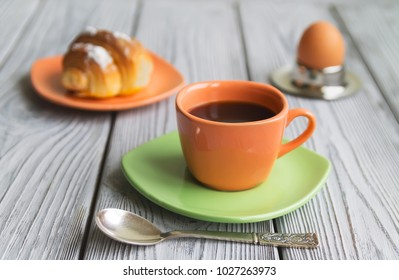 breakfast an egg of a coffee croissant on a wooden background