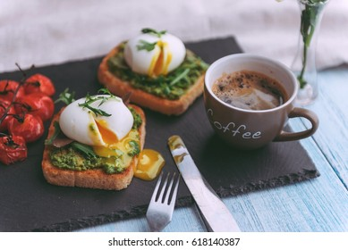 Breakfast with egg poached on avocado paddle and basil and a cup of coffee