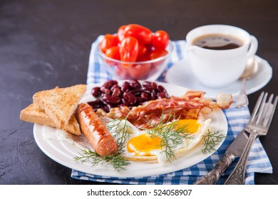 breakfast - egg, sausage, bacon and haricot in a plate on a table, selective focus, copy space