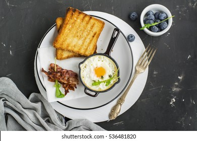 Breakfast of eggs in the batch iron frying pan with crispy bacon and toast with berries fresh blueberries on a dark background. Top view