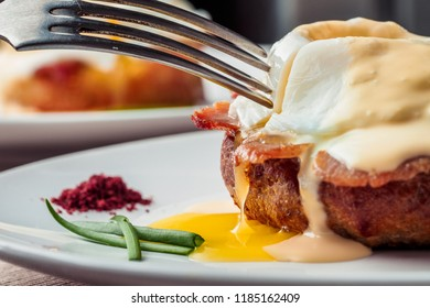 Breakfast is Eggs Benedict - toasted English muffins, bacon, ham, poached eggs, herbs and delicious buttery hollandaise sauce. Close-up image. Shallow depth of field.