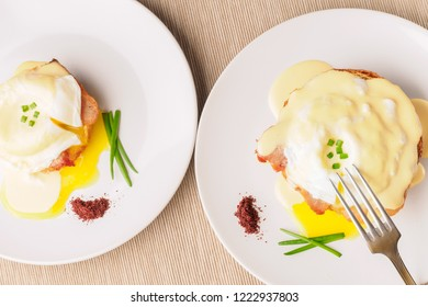 Breakfast is Eggs Benedict - toasted English muffins, bacon, ham, poached eggs, herbs and delicious buttery hollandaise sauce. Two white plate and fork. Top view . Space for text.