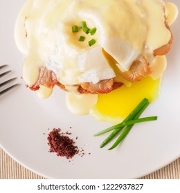 Breakfast is Eggs Benedict - toasted English muffins, bacon, ham, poached eggs, herbs and delicious buttery hollandaise sauce. White plate and fork. Top view . Space for text.