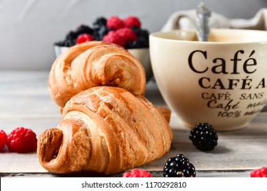 Breakfast at the European hotel: coffee with milk and croissants, jam and fresh raspberries and blackberries on a wooden table. on the Cup inscription in French (mocha coffee, coffee with milk)