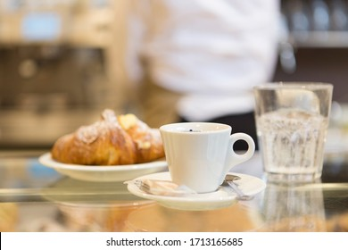 Breakfast in a fast food, detail of coffee cup and croissant.