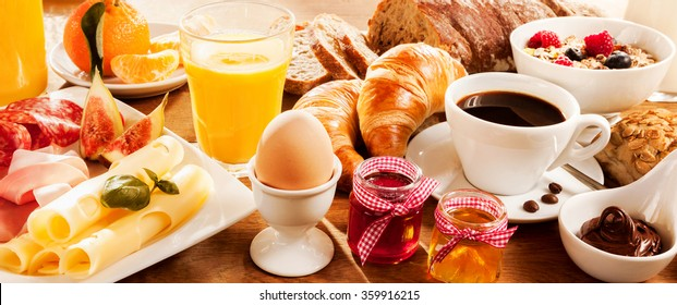 Breakfast feast with egg, meat, bread, coffee and juice