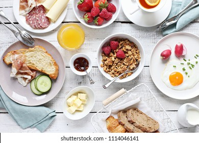 Breakfast food table. Brunch set, meal variety with fried egg, croissants, granola and fresh strawberry. Overhead view