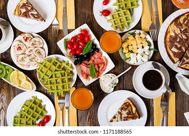 Breakfast food table. Festive brunch set, meal variety with spinach waffles, salmon, cheese, olives, chicken rolls and cheesecake. Top view. Flat lay