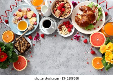 Breakfast food table. Festive brunch set, meal variety with pancakes, croissant, juice, granola and fresh fruits. Easter breakfast. Top view with copy space.