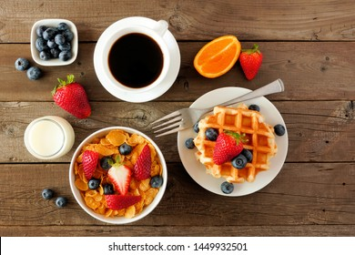 Breakfast food table scene. Fruits, cereal, waffles, milk and coffee. Top view over a dark wood background.