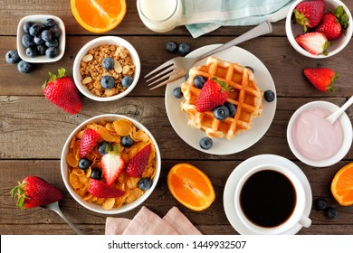 Breakfast food table scene. Fruits, cereal, waffles, yogurt and coffee. Top view over a dark wood background.